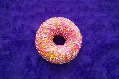 Donut pink icing background purple space for text Stock Photo