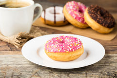 Donut with pink icing and sprinkles with coffee Royalty Free Stock Images