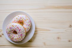 Donut on a plate and on a wooden table. Photo of sweets. Royalty Free Stock Image