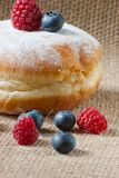Donut with powdered sugar and fresh berries. Healthy food vs. junk food Royalty Free Stock Photos