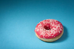Donut with red icing isolated on blue background Royalty Free Stock Photography
