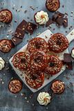 Donut rings and vanilla caramel cupcakes with white and dark chocolate chippings and icing served on board Stock Image