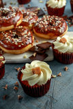 Donut rings and vanilla caramel cupcakes with white and dark chocolate chippings and icing served on board Stock Photo
