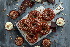 Donut rings and vanilla caramel cupcakes with white and dark chocolate chippings and icing served on board Royalty Free Stock Images