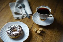 Donut sprinkled with chocolate chips, a cup of black tea, a linen napkin, sugar pieces on a wooden table. Cozy cafe. stock photos