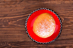 Donut sprinkled with powdered on a red saucer Royalty Free Stock Photos