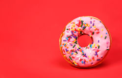 Donut with sprinkles over red royalty free stock photo