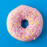 Donut with sprinkles and pink frosting on blue background. From above stock photos