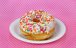 Donut with sprinkles on a plate Stock Photography