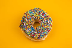 Donut with sprinkles on yellow background Royalty Free Stock Photos