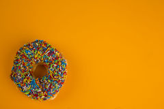 Donut with sprinkles on yellow background Stock Photos