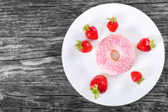 Donut with Strawberry Icing on white dish. top view Stock Photos