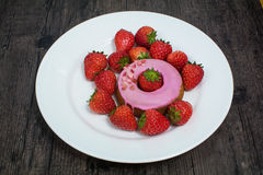 Donut and strawberry on the plate. Strawberry and fruit donut on the white plate on the wooden table Stock Image