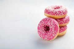 Donut. Sweet icing sugar food. Dessert colorful snack.Treat from delicious pastry breakfast. Bakery cake. Doughnut with frosting. Baked unhealthy round on a Stock Photos