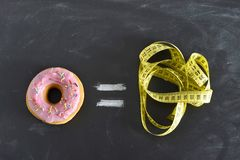 Donut and tailor measure tape on blackboard in sugar sweet abuse and addiction equal body overweight. Donut and tailor measure tape on blackboard representing Stock Photos