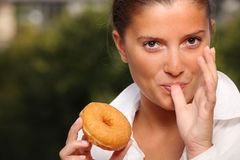 Donut temptation. A picture of a woman trying to resist temptation of eating a donut over natural background stock photography
