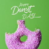 Donut and text happy donut day. A nibbled appetizing donut coated with a pink frosting and white sprinkles and the text happy donut day against a bright green Royalty Free Stock Photo