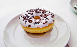Donut with vanilla white glaze and chocolate sprinkles Royalty Free Stock Photo