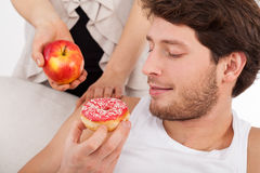 Donut versus apple Stock Images