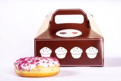 Donut vor Kasten Stockfotografie