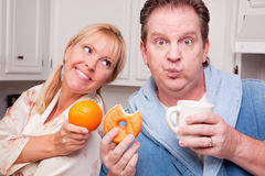 Donut vs. Fruit Healthy Eating Decision. Couple in Kitchen Eating Donut and Coffee or Healthy Fruit Royalty Free Stock Images