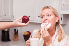 Donut vs. Fruit Healthy Eating Decision. Couple in Kitchen Eating Donut and Coffee or Healthy Fruit Stock Photos