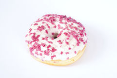 Donut with white glazing and pink sprinkles. Dough-nut isolated on white background view from above Stock Image