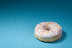 Donut with white icing isolated on blue background Stock Photo