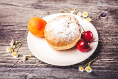 Donut on white plate. With fruits on wooden background Royalty Free Stock Photos