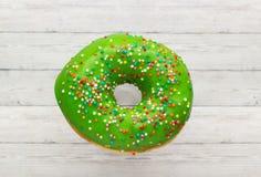 Donutgrün mit besprüht lokalisiert auf hölzernem Hintergrund, Nahaufnahme lizenzfreies stockfoto
