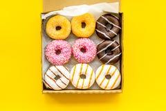 Donuts με τις διαφορετικές γεύσεις στο κιβώτιο στο κίτρινο πρότυπο άποψης υποβάθρου τοπ στοκ εικόνες με δικαίωμα ελεύθερης χρήσης