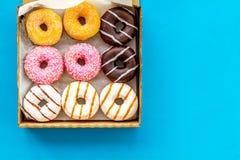 Donuts με τις διαφορετικές γεύσεις στο κιβώτιο στο μπλε πρότυπο άποψης υποβάθρου τοπ στοκ εικόνες