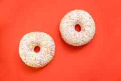 Donuts με την τήξη στο κόκκινο υπόβαθρο Γλυκά donuts, επιδόρπιο πρωινού Εύγευστα ζωηρόχρωμα donuts που απομονώνονται διάστημα αντ Στοκ εικόνα με δικαίωμα ελεύθερης χρήσης