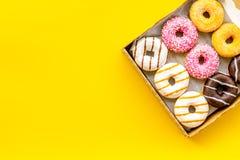 Donuts με τις διαφορετικές γεύσεις στο κιβώτιο στο κίτρινο πρότυπο άποψης υποβάθρου τοπ στοκ φωτογραφία