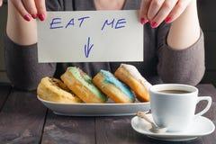 Donuts взятия женщины и сообщение владением едят меня Стоковые Изображения RF
