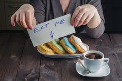 Donuts взятия женщины и сообщение владением едят меня Стоковое Изображение RF