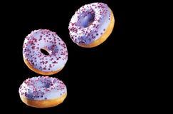3 donuts в движении изолированного на черноте Стоковая Фотография