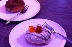 2 donuts в пинке с хлопьями кокоса и белом шоколаде служили на донуте плиты и карамельки на заднем плане на деревянном взгляде Стоковые Фотографии RF