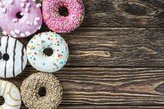 Donuts в поливе сортировали на деревянном Стоковые Изображения RF