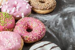 Donuts в поливе сортировали на черноте Стоковая Фотография