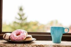 Donuts и младенец чашки кофе следующий силл окна Стоковое фото RF