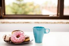 Donuts и младенец чашки кофе следующий силл окна Стоковое Фото
