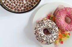 Donuts и хлопья мозоли на белой предпосылке стоковые фото