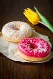 Donuts и цветок тюльпана на коричневой предпосылке Стоковые Изображения RF