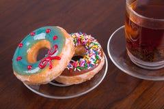 Donuts и чашка чаю на деревянном столе Стоковое Изображение RF