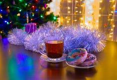 Donuts и чашка чаю на предпосылке рождества Стоковое фото RF