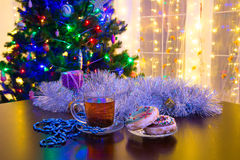 Donuts и чашка чаю на предпосылке рождества Стоковое Фото