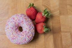 Donuts клубники на деревянной предпосылке Стоковое Фото