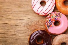 Donuts на деревянной предпосылке Стоковые Изображения