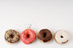 Donuts на плите на белой предпосылке Стоковые Изображения